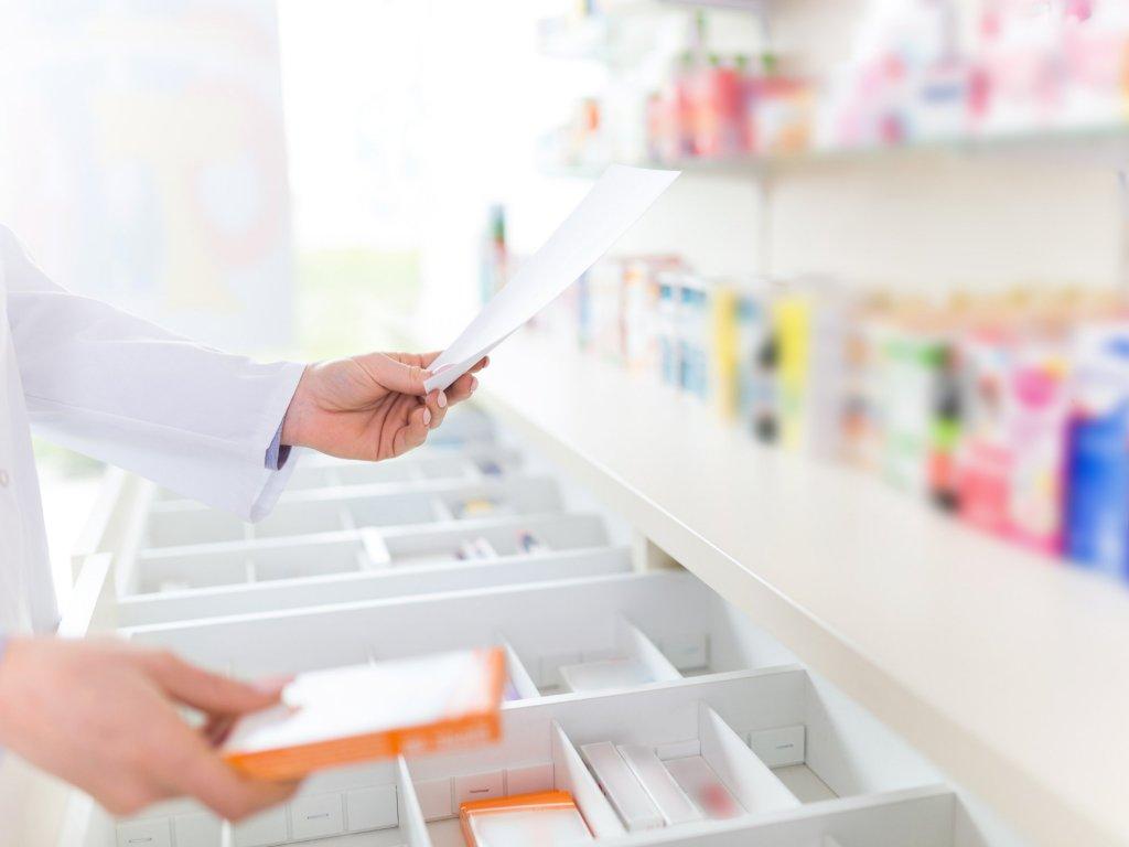 Pharmacist holding prescription in Pharmacy